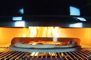 Pizza auf dem Pizzastein im Gasgrill